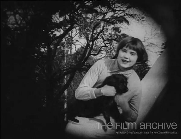 Freda Crosher plays with a dog.
