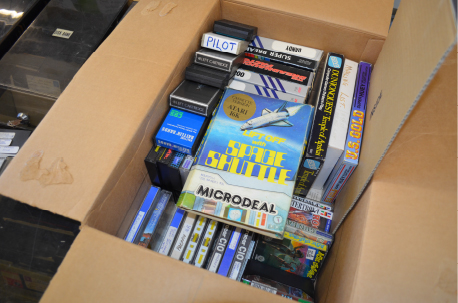 Box of 8-bit data cassettes and games cartridges.