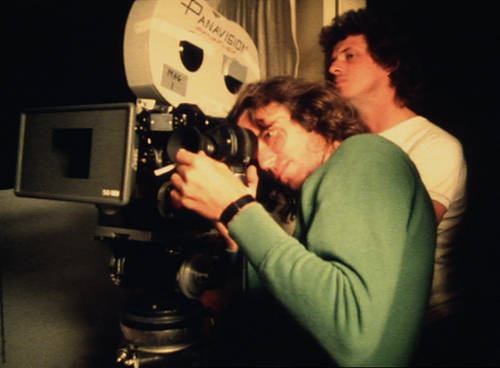 Roger Donaldson frames up a shot, while a crew member keeps an eye on the action on-set. Who would have guessed he'd go on to direct Cocktail (1988)?