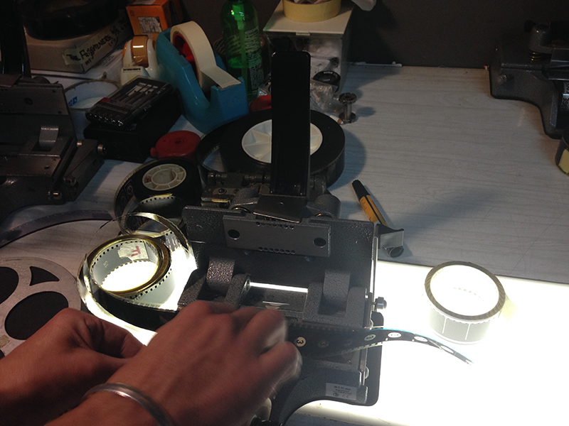 Oscar splicing a leader onto a film. The number 3 is visible, counting down the seconds until the film starts.