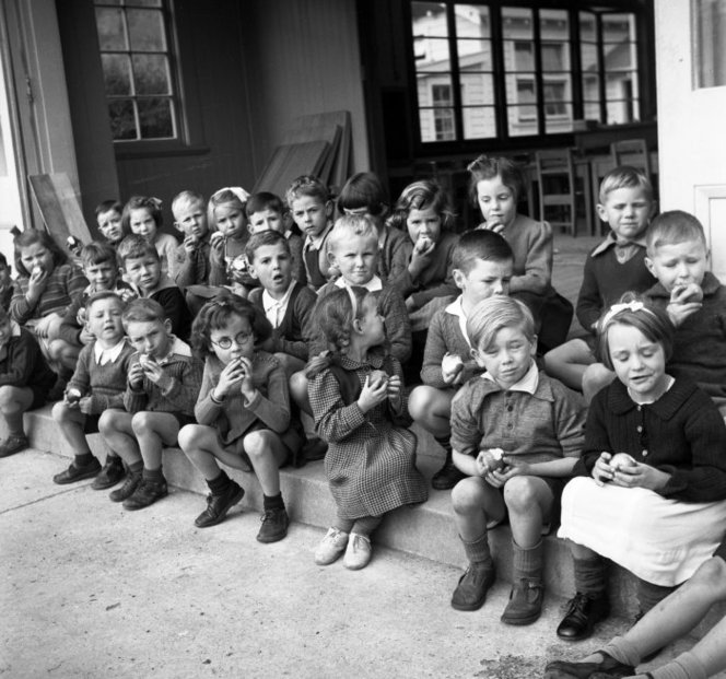 Primary school children eating apples. Pascoe, John Dobree, 1908-1972 :Photographic albums, prints and negatives. Ref: 1/4-001007-F. Alexander Turnbull Library, Wellington, New Zealand. http://natlib.govt.nz/records/23113216