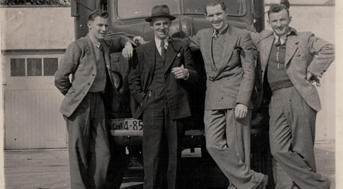 """Brian Cosnett (technician), Leo Fowler (producer), Geoff Haggett (commentator) and Dick Miller (technician) pose with the faithful """"Gertie,"""" the Mobile Unit recording truck, in 1947 or 1948 (Ngā Taonga Sound & Vision collection)."""