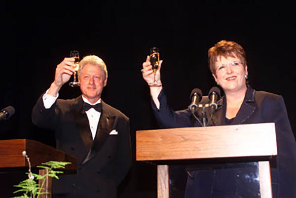 United States President Bill Clinton and New Zealand Prime Minister Jenny Shipley join in a toast during a gala at the Royal New Zealand Air Force Museum in Christchurch, 15 September 1999. Photo by David Scull (public domain image).