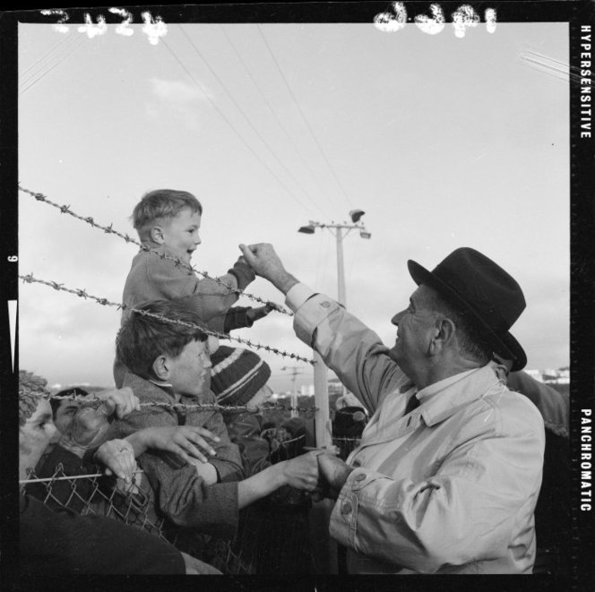American President Lyndon Baines Johnson shaking the hand of Clem Thorn, aged five years, while he sits on his father's shoulders amongst the crowd at Wellington Airport. Photographed by an Evening Post staff photographer on the 20th of October 1966. http://natlib.govt.nz/records/23083703
