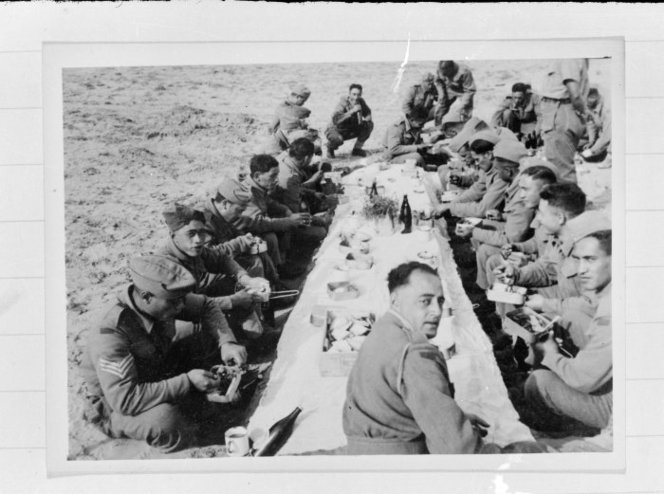 Members of the 28 (Māori) Battalion eating Christmas Dinner in the desert, Nofilia (Libya), on Christmas Day of 1942. Shows soldiers in uniform sitting cross-legged on the sand around a make-shift table, drinking beer and eating food from tins. Photograph taken on 25 Dec 1942, by Dr C N D'Arcy. http://natlib.govt.nz/records/23118353
