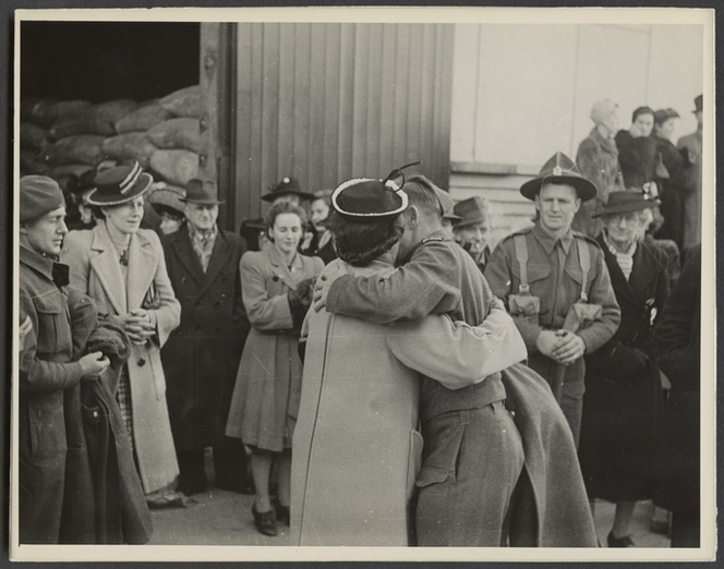 World War II servicemen being embraced after his return to Wellington on the hospital ship Wanganella - Photograph taken by Government Film Studios. Pascoe, John Dobree, 1908-1972: Photographic albums, prints and negatives. Ref: PAColl-0783-2-0386. Alexander Turnbull Library, Wellington, New Zealand. http://natlib.govt.nz/records/22745112