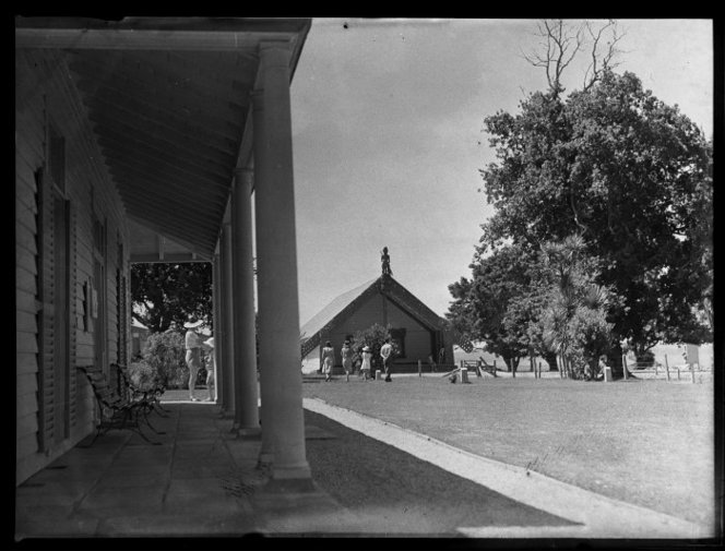 View of the verandah of the Treaty house, Waitangi, New Zealand, looking east across the grounds and including the meeting house. Photographed by Whites Aviation in 1947. http://natlib.govt.nz/records/23157208