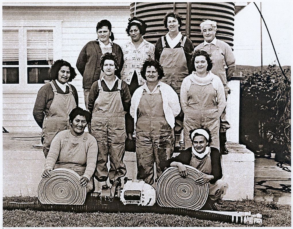 The Ahipara Women's Fire Brigade. Back row: Harriet Pure, Hinemoa Te Paa, Linda Curie, Doris Hales. Middle row: Api Kīngi, Joyce Hunt, Jackie Saunders, Mary Hanlon. Front row: Peggy Adams, Agnes Rakich. Photo by Bruce Rogers, supplied courtesy of Te Ahu Museum and Archive, Kaitaia.
