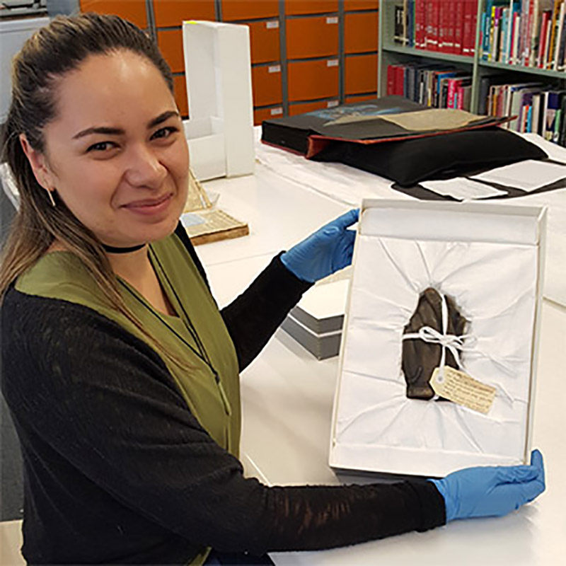 Jasmine Te Hira presents her rehousing skills in our Jonathan Dennis Library. Photo by Mishelle Muagututi'a
