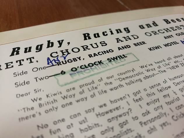 "Rugby, Racing & Beer – Rod Derrett HMV 7EGM 6070 – showing 'PROHIBITED' stamp and yellow scoring and deliberate scratching to prevent playing the track ""6 O'Clock Swill.""  Ngā Taonga Sound & Vision ID19077"