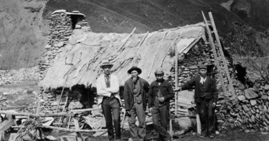 miners standing outside stone hut