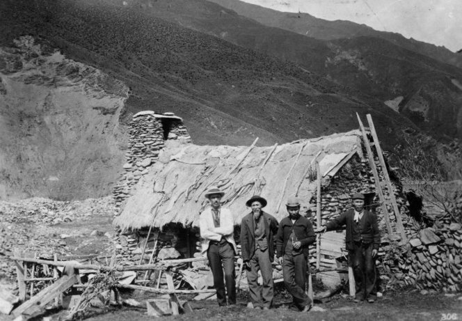 Black and white photo shows gold miners outside an old stone cottage