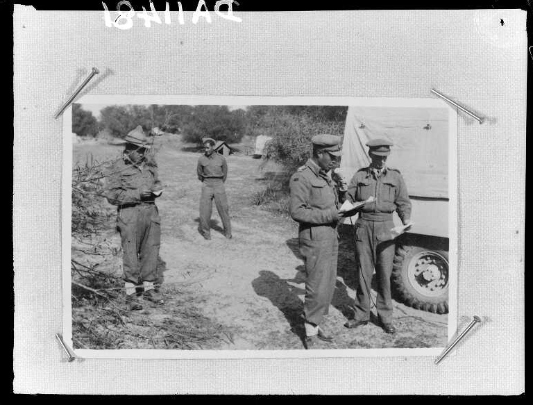 Māori Battalion soldiers stand next to a truck
