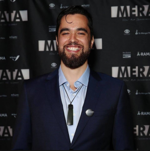 Young Māori man in a suit, smiling