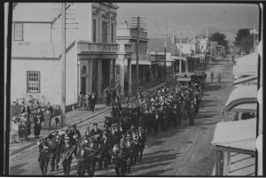 A brass band leads the funeral procession and glass drawn hearse, followed by people and cars along the main street of Ōtaki to the urupā at the rear of the Rangiātea Church. Photography Charles Frederick Newham. Filmed by NZ Moving Picture Company, Māoriland Films. Stills Collection, Ngā Taonga Sound & Vision.