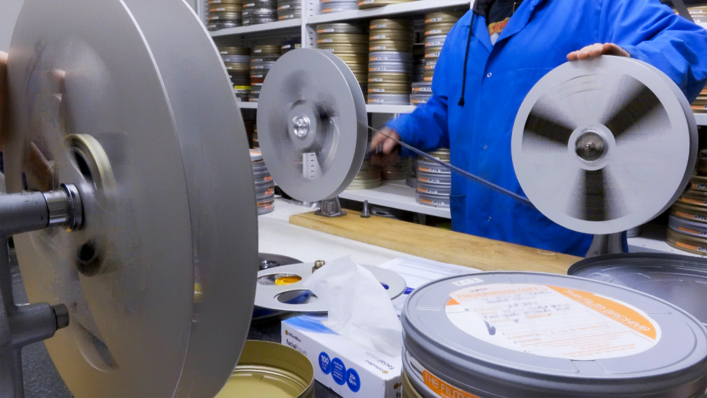 A staff member winds a film off its old reel and onto a new one