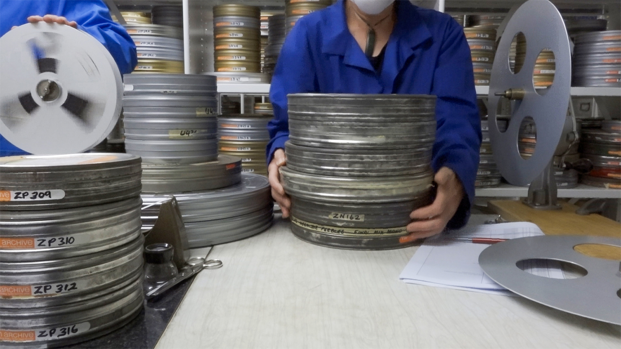 A staff member lifts a stack of film cans