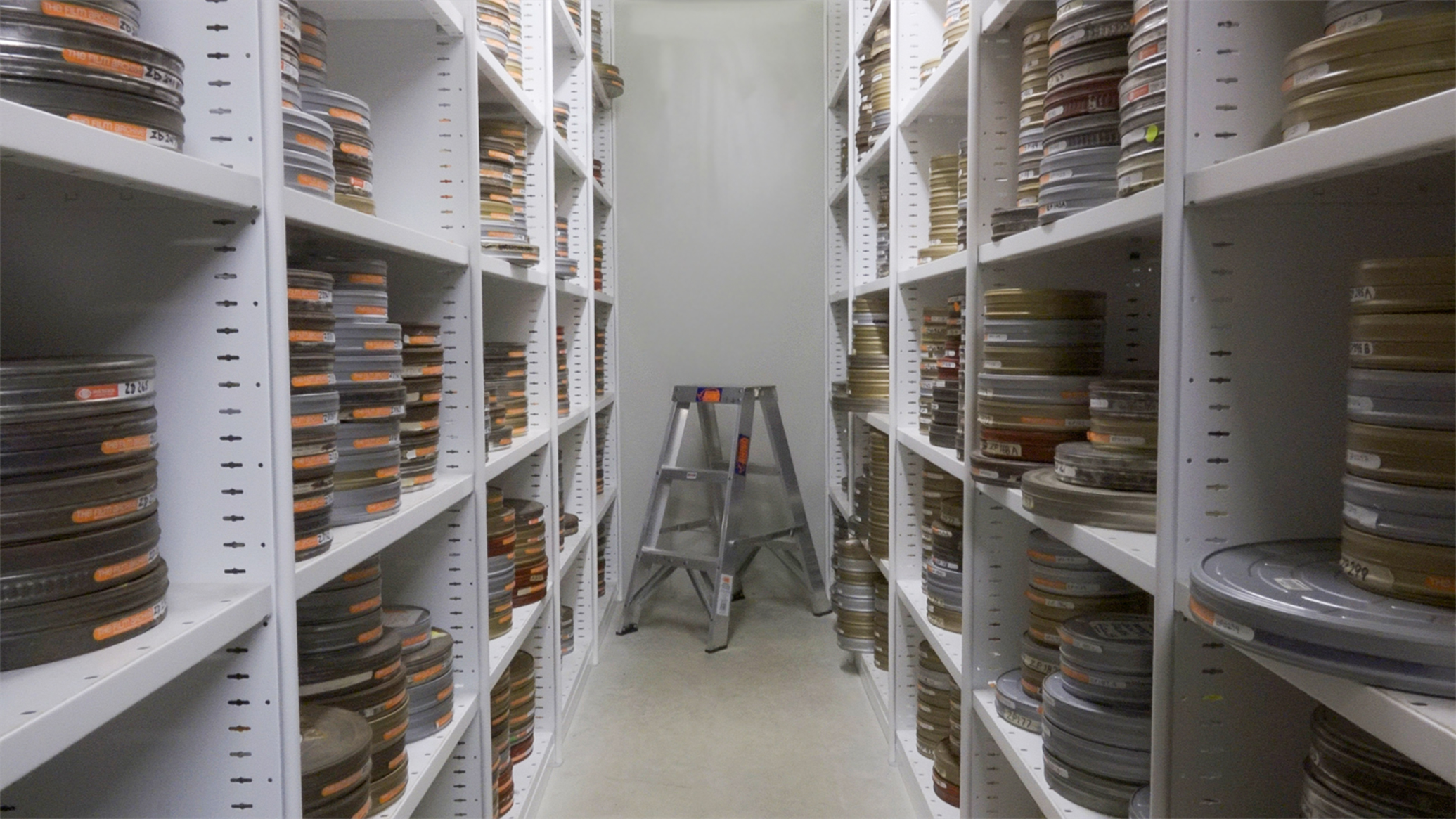 View of two long shelves with stacks of film cans