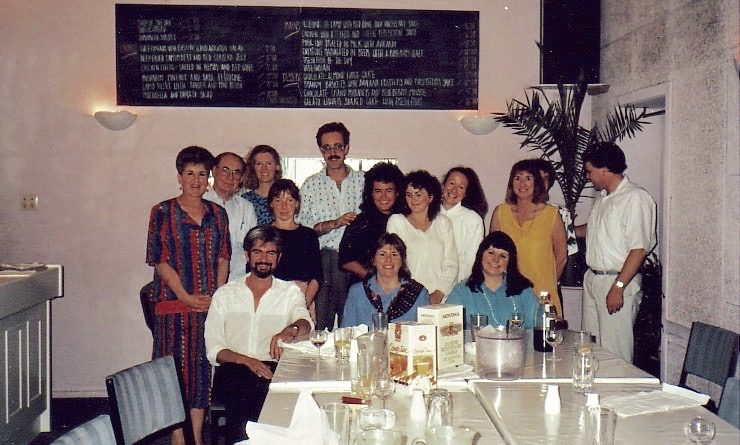 A small group of people in 1980s era clothing at a restaurant