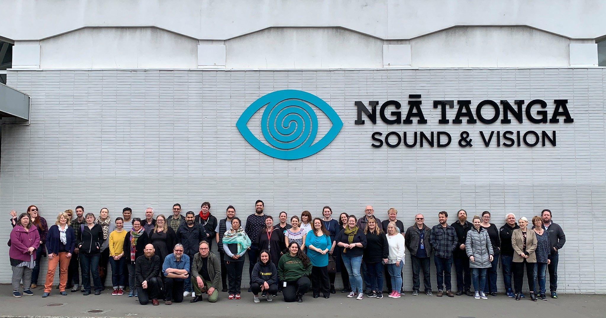 Nga Taonga staff group photo standing outside the Taranaki St premises